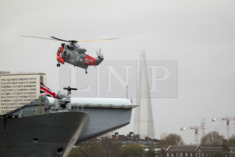 © Licensed to London News Pictures. 08/05/2013. London, UK.  Royal Navy sea king helicopter  lands on HMS Illustrious. A Royal Navy flypast, including a Sea King and Merlin, over Greenwich as part of events to mark the 70th anniversary of the Battle of the Atlantic. The fly past was shown live on BBC1 on the One Show.. Photo credit : Rob Powell/LNP