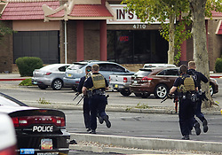 October 7, 2018 - Albuquerque, New Mexico, U.S. - Albuquerque Police Officers take position in the parking lot during a hostage situation at Lin's Buffet located near Montgomery and Monroe N.E. A man was shot by police following a string of crimes that ended in taking hostages inside of the Chinese buffet where around 80 people were working and dining. (Credit Image: © Adolphe Pierre-Louis/Albuquerque Journal via ZUMA Wire)