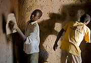 Brothers Emma and Albert use a cassava porridge, sand and cow dung cement to plaster the wall of a hut.