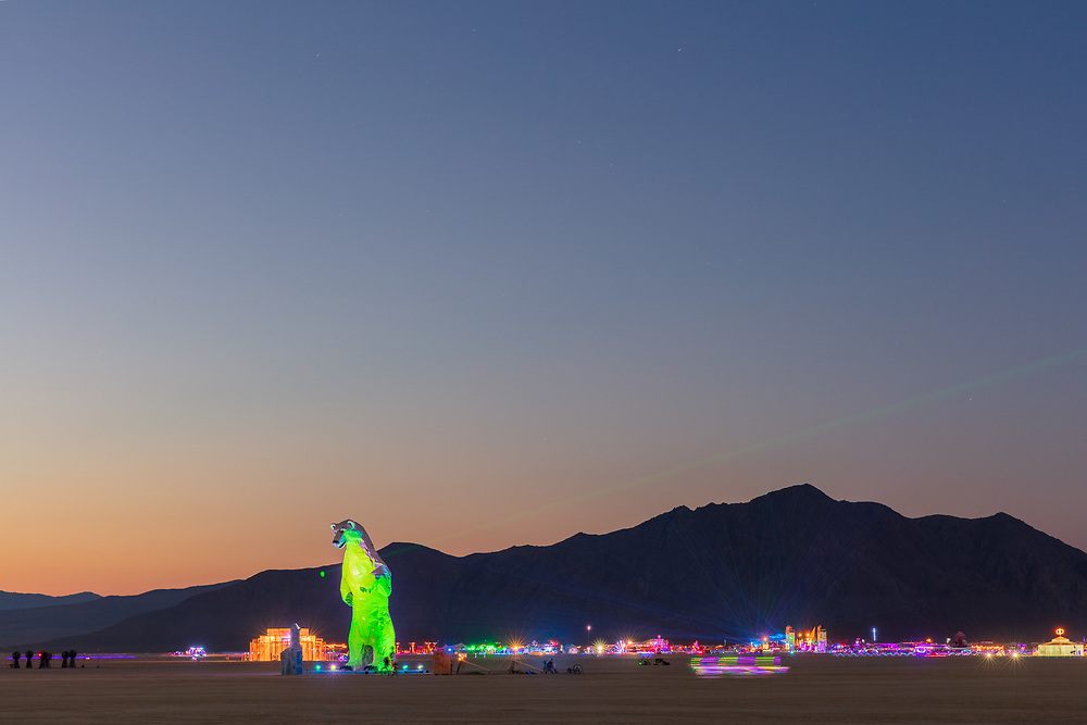 """Long View, a polar bear stands in the desert by: Don Kennell and Arctic Burn 505 from: Santa Fe, NM year: 2018<br /> <br /> A 34 foot polar bear made from white car hoods looks across the boundless vista of Black Rock City. The polar bear is an unlikely visitor to the Playa made from materials transformed from another time and place. Manifesting forces of climate change, she is searching for allies. Taking the """"Long View"""" is crucial to survival. Combining content and joy, we ask the viewer to develop a relationship with the animal. Polar bears help humans imagine a faraway place, a place most will never visit. They are uniquely positioned as ambassadors to bring the arctic into human awareness. Animals disappear to make room for our cars. Turning wrecked cars into monumental animals visually reverses this process and impacts the consciousness of the viewer. Contact: arcticburn505@gmail.com"""