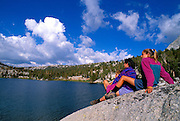 Family relaxing on the shore of Boothe Lake in the Cathedral Range, Sierra Nevada Mountains, Yosemite National Park, California.