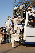 Local men climb aboard a busy bus in Agra, India