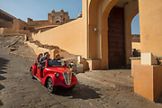 Electric car with tourists seeing the Amber Fort, created in the late 16th century, on 4th February 2018 in Amer Jaipur, Rajasthan, India. Constructed of red sandstone and marble, the attractive, opulent palace is laid out on four levels, each with a courtyard. It consists of the Diwan-e-Aam, or Hall of Public Audience, the Diwan-e-Khas, or Hall of Private Audience, the Sheesh Mahal mirror palace, or Jai Mandir, and the Sukh Niwas where a cool climate is artificially created by winds that blow over a water cascade within the palace. Hence, the Amer Fort is also popularly known as the Amer Palace. The most popular tourist destination of Jaipur it recieves over 5000 visitirs daily.