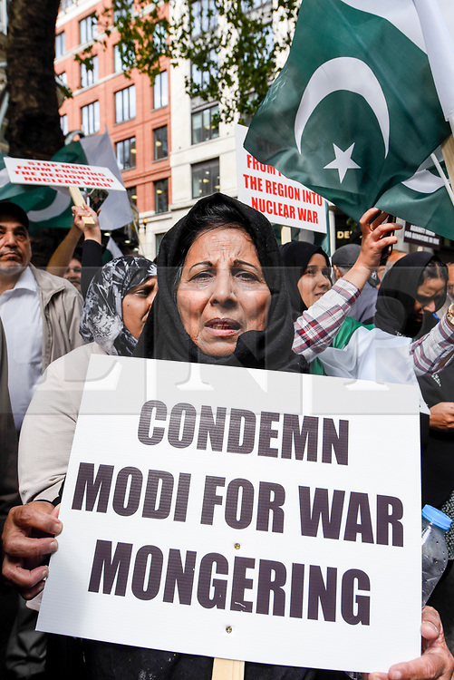 © Licensed to London News Pictures. 15/08/2019. LONDON, UK.  A woman joins thousands of protesters, many waving Pakistani and Kashmiri flags, outside the Indian High Commission in Aldwych, on what they are calling Black Day, to stand in solidarity with the people of Kashmir.  Indian Prime Minister Narendra Modi delivered an Independence Day speech highlighting his decision to remove the special rights of Kashmir as an autonomous region.  Photo credit: Stephen Chung/LNP