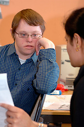 Man with learning disabilities filling in form with carer at community centre; Bradford Yorkshire UK