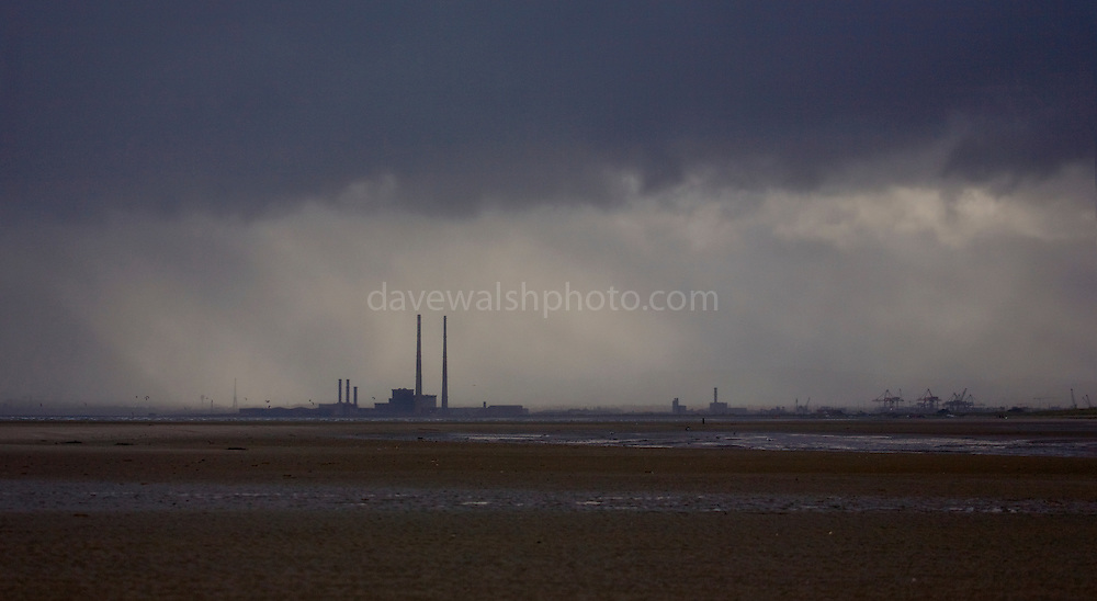 View of the 207m chimney stacks of  Poolbeg electricity generating station from Dollymount, Bull Island, Dublin. The energy generating power station is Ireland's second most polluting installation in terms of carbon dioxide, co2 emissions. Bull Island is a UNESCO protected biosphere reserve in the Northern suburbs of Dublin. It features two golf clubs, and Dollymount beach, used for kitesurfing and other outdoor activities. Wildlife includes seals and bird life.