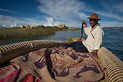 Uros  boy paddlling a totora reed boat around a floating island on Lake Titicaca, Peru