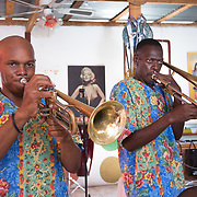 CAPTION: Brass musicians in Troupe Dahomey's band. The IAF has helped Troupe Dahomey in a big way with getting its studio project off the ground. During Carnival season, there frequently aren't enough studio spaces in Haiti, meaning that local people looking to record traditional Haitian music don't have a place to go; this studio will make this problem a thing of the past. ORGANIZATION: Troupe Dahomey / Sant Pont Ayiti (SPA). LOCATION: La Fleur du Chaine, Rue Capois, Port-au-Prince, Haiti. INDIVIDUAL(S) PHOTOGRAPHED: Danoël Jeorn Worlf (left) and Moril Jean Fritz (right).