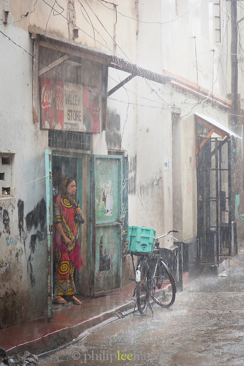 A woman shelters from the pouring rain in Mombasa, Kenya