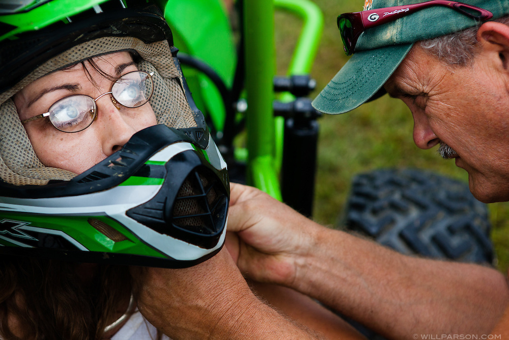 """Mick Hart, from Coolville, Ohio, adjusts the helmet of his wife Christy Hart before her first race of the day during the Swampstock mud bog races in Coolville, Sept. 1, 2012. """"He likes to fix it and I like to drive it…wide open!"""" Hart said."""