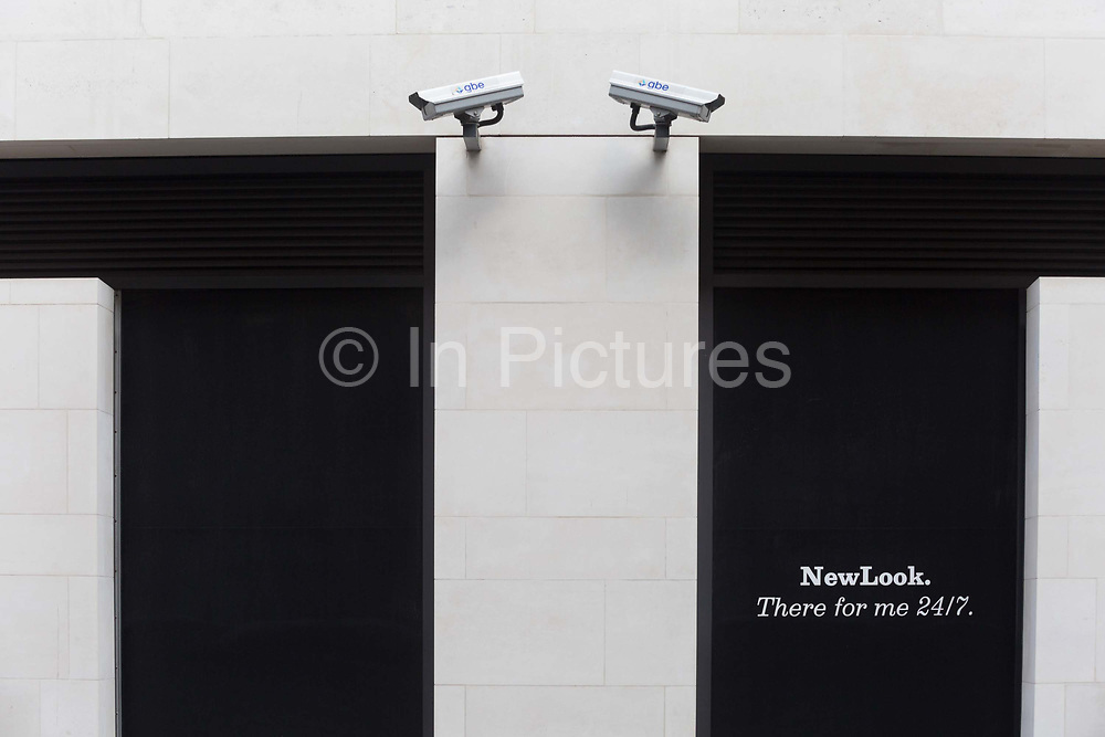 Two CCTV cameras on a wall outside a shop of New Look, in the City of London, one of the most-watched cities in the world, on 11th August, 2017, in London, England. According to 2011 figures, there are 420,000 CCTV cameras in London.