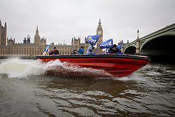 © Licensed to London News Pictures. 25/02/2013. London, UK. Maritime campaigners in boats are seen at a press call on the River Thames opposite the Houses of Parliament in London today (25/02/13). The campaigners, from the Marine Conservation Society, are part of a larger protest held with 'Fish Fight campaigner Hugh Fearnley-Whittingstall, which aims to call for 127 marine conservation zones to protect marine wildlife around the UK. Photo credit: Matt Cetti-Roberts/LNP