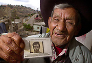 Standing in front of his modest Tijuana home he shares with family members DIONISIO MADERA LOPEZ holds his Alien Laborer's Identification Card from his days as a bracero farm laborer.  U/T photo CHARLIE NEUMAN
