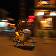 A vietnamese lady pedals past a lantern lit street corner at night time in Hoi An, Vietnam. Hoi An is an ancient town and an exceptionally well-preserved example of a South-East Asian trading port dating from the 15th century. Hoi An is now a major tourist attraction because of its history. Hoi An, Vietnam. 5th March 2012. Photo Tim Clayton