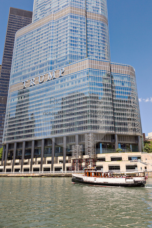 A boat tour travels down the Chicago River past the Trump Tower on a summers day in Chicago, Illinois, USA