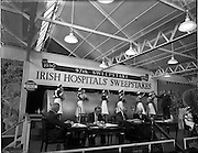 22/10/1959<br /> 10/22/1959<br /> 22 October 1959<br /> Irish Hospitals Trust 97th Sweepstake Draw on Cambridgeshire 1959 at Irish Hospital Sweepstakes office, Ballsbridge, Dublin. General view of the platform showing the drum, officials and nurses with a Garda Superintendent taking a drawn number from one of the nurses.
