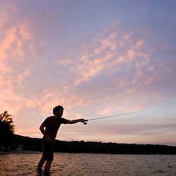 A man fishing at sunset on Lake Sunapee at Mount Sunapee State Park in Newbury, New Hampshire.