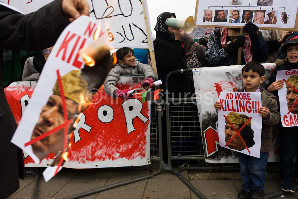 Exiled Libyan children participate in the demand for the death dictator Colonel Gaddafi during protests opposite their London embassy during the uprising. A man walks past with a print of Gaddafi's face, flames licking around his head and the children – two young boys – watch as they hold their own posters that read No More Killing – calling for an end to the leader's atrocities against his own people.