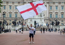 Licensed to London News Pictures. 11/07/2021. London, UK. England fan Steven Knott 39 from Birmingham waves a giant flags next to Buckingham Palace, London ahead of England's Euro 2020 finals match. England take on Italy in the Euro 2020 final at the iconic Wembley Stadium this evening. Photo credit: Alex Lentati/LNP