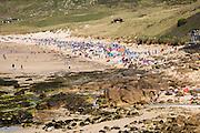 Busy crowded sandy beach, Sennan Cove, Land's End, Cornwall, England, UK