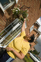 Older woman pruning the flowers in her hanging basket,