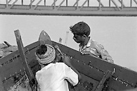 India, Uttar Pradesh; Varanasi, 1999. One to back the plank against the hammer's blow, the other to strike home a handmade tarred nail, these Varanasi boat builders are experts.