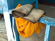 An old Lao manuscript and an orange monk's robe at the 480 year old temple in Ban Mouanghoun, Phongsaly province, Lao PDR. Although there are several villages with temples along the Nam Ou river, the remote and roadless Ban Mouanghoun is the only village in this area with its own resident monks who are also required to perform ceremonies at all the local villages. The village will be relocated due to the construction of the Nam Ou Cascade Hydropower project Dam 5.