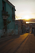 Street scene at dusk with golden light, Santiago de Cuba, Cuba. .