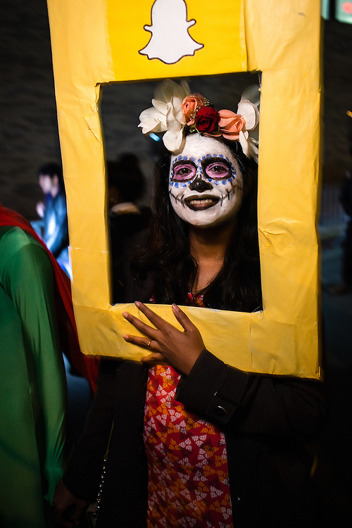 New York, NY - 31 October 2016. A woman with face painted as La Calavera Catrina behind a Snapchat frame  in the Greenwich Village Halloween Parade.