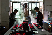 Workers iron football scarves at the Yiwu Wells Knitting Products Co., Ltd factory in Yiwu, Zhejiang Province, China on 06 March  2013.<br /> The city of Yiwu is known as one of China's largest trading centers for small merchandise and light industry, drawing buyers from around the world. Uncertain global demand, a stronger yuan currency and rising labour costs have taken their toll on Chinese exporters, but analysts believe sales could pick up modestly in 2014 due to improved demand from the United States and Europe.