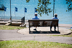An elderly couple sitting on a seaside bench but apart and not interacting with each other.