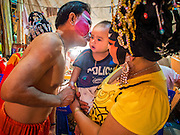"26 NOVEMBER 2014 - BANGKOK, THAILAND:  Chinese opera performers with their child backstage at a Chinese opera at the Chow Su Kong Shrine in the Talat Noi neighborhood of Bangkok. Chinese opera was once very popular in Thailand, where it is called ""Ngiew."" It is usually performed in the Teochew language. Millions of Chinese emigrated to Thailand (then Siam) in the 18th and 19th centuries and brought their culture with them. Recently the popularity of ngiew has faded as people turn to performances of opera on DVD or movies. There are about 30 Chinese opera troupes left in Bangkok and its environs. They are especially busy during Chinese New Year and Chinese holidays when they travel from Chinese temple to Chinese temple performing on stages they put up in streets near the temple, sometimes sleeping on hammocks they sling under their stage.     PHOTO BY JACK KURTZ"
