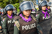 22 DECEMBER 2013 - BANGKOK, THAILAND: Women Thai riot police retreat from a road block in front of the home of caretaker Prime Minister Yingluck Shinawatra during a protest Sunday. Hundreds of thousands of Thais gathered in Bangkok Sunday in a series of protests against the caretaker government of Yingluck Shinawatra. The protests are a continuation of protests that started in early November and have caused the dissolution of the Pheu Thai led government of Yingluck Shinawatra. Protestors congregated at home of Yingluck and launched a series of motorcades that effectively gridlocked the city. Yingluck was not home when protestors picketed her home.     PHOTO BY JACK KURTZ