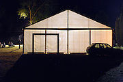 people standing and sitting outside a large event tent