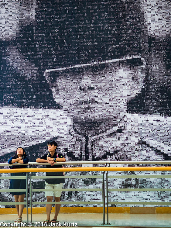 """06 NOVEMBER 2016 - BANGKOK, THAILAND: Thais stand in front of a large mosaic photo of Bhumibol Adulyadej, the late King of Thailand at the Bangkok Art and Culture Centre. The Royal Photographic Society of Thailand with the Bangkok Art and Culture Centre and Thai Beverage Public Company Limited are hosting a photography exhibition to commemorate the late Thai King Bhumibol Adulyadej. The """"In Remembrance of His Majesty King Bhumibol Adulyadej"""" Photography Exhibition is dsiplaying 89 photographs by 89 photographers honoring King Bhumibol Adulyadej's legacy. The King was an avid photographer was usually seen with a camera in his hands. The exhibition will be on display until 27 November 2016 on the Curved Walls on the 3rd - 5th floor, Bangkok Art and Culture Centre.     PHOTO BY JACK KURTZ"""