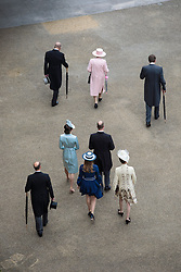 Queen Elizabeth II and the Duke of Edinburgh (both top left) lead members of the Royal family to greet guests at a garden party at Buckingham Palace in London.