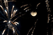 A perigee full moon, also known as a supermoon, shares the sky with fireworks during a display in Chester, New York.  The full moons of August and September will also be supermoons.