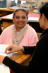 Woman with learning disabilities filling in form with carer at community centre; Bradford Yorkshire UK