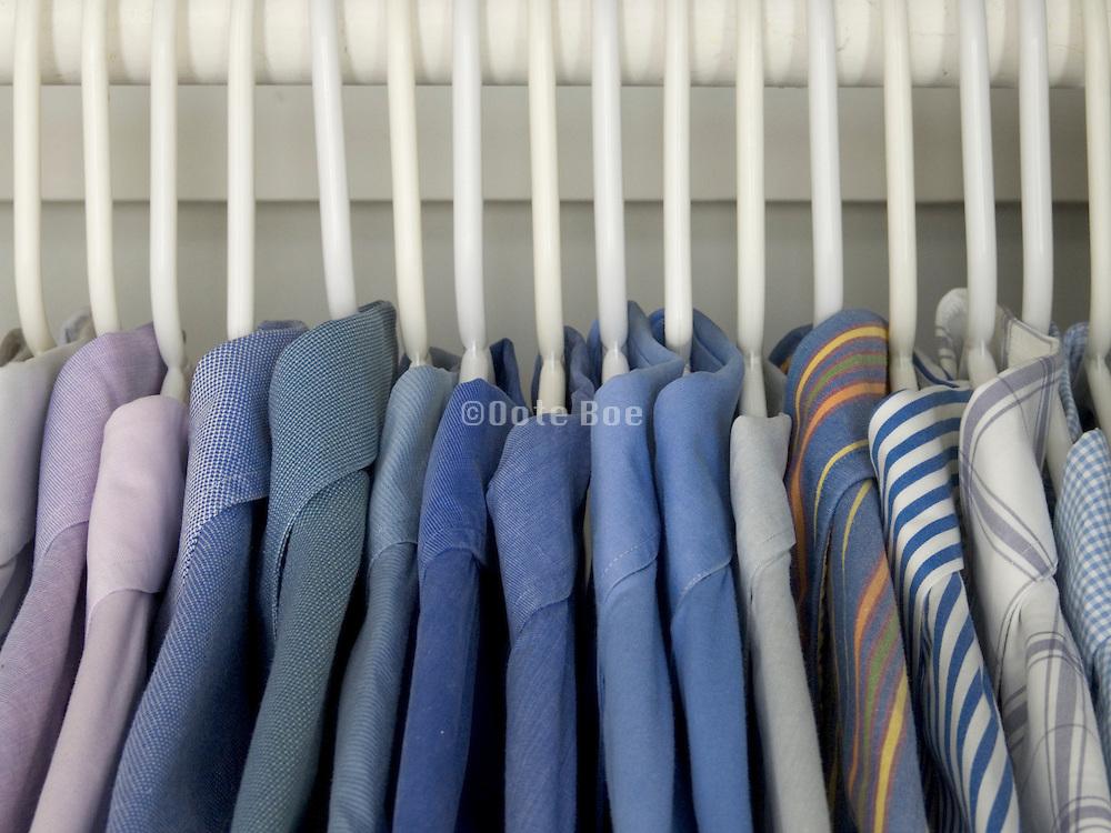 men shirts hanging in a closet.