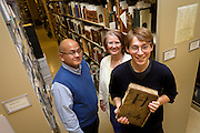 Tad Boehmer '12 poses for a portrait alongside his MAP advisors, Classics professor Angelo Mercado and librarian Catherine Rod, in the archives vault in the basement of Burling Library. Boehmer's project sought to determine the origin and use of an unidentified, 488-page manuscript written primarily in Latin. BEN BREWER/Grinnell College