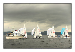 470 Class European Championships Largs - Day 1.Racing in grey and variable conditions on the Clyde..Finish line, GBR852, Philip SPARKS, David KOHLER, RLYC, GER10, Ferdinand GERZ, Patrick FOLLMANN, TUR890, Deniz CINAR, Ates CINAR, and AUT437, David BARGEHR, Lukas MAHR