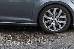 A car's tyre absorbs some of the impact as it passes through a pothole on Sidmouth Road in Willesden Green, west London, as the recent cold, wet weather has given rise to the increase in potholes and road surface deterioration in the capital. London, March 28 2018.