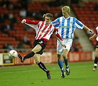 Photo. Andrew Unwin<br /> Sunderland v Huddersfield Town, Carling Cup Second Round, Stadium of Light, Sunderland 23/09/2003.<br /> Sunderland's George McCartney (l) clears the ball from Huddersfield Town's Jon Stead (r).
