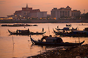 FISHERMEN MEKONG RIVER. South East Asia, Cambodia, Phnom Penh, Mekong River. The Cham fisher people live in various desolated villages along the banks of the Mekong and Tonle Sap rivers. The fisher families live like river gypsy nomads, working and living on their boats, sleeping under a sprung bamboo frame, all their worldly goods stored below deck. They live in extended families, with numerous boats, together for safety. Their diet is rice, vegetables and fish. Their sleek wooden boats are powered by petrol outboard motors with batteries or generators to supply lighting at night. Their fishing technique is laying nets twice or three times per day, which are weighted well below the surface, using old paint aerosal canisters as buoyant floaters, hanging just beneath the surface. These particular fisher families, living at the junction of the Mekong and Tonle Sap rivers, overlooked by Phnom Penh, sell their catch at the Vietnamese market, on the banks of the river. Their life and fortunes are controlled by the cycle of the river. As the river levels drop, so the quantity of fish decreases, until after the heavy floods of the monsoon they fill the river again. They are poor traditional Muslims, marginalised from mainstream society, living a third world life in the immmediate shadow of the first world. The Cham, originally a people of an ancient kingdom called Champa, are a small and disenfranchised community who were disinherited of their land. They are a socially important ethnic group in Cambodia, numbering close to 300,000. The Cham people, live in some 400 villages across Kampong Chnang and Kampong Cham provinces. Their religion is Muslim and their language belongs to the Malayo-Polynesian family. Their livelihoods are as diverse as rice farming, cattle trading, hunting and fishing.///Cham fishing boats, silhouetted against water, with a backdrop of Phnom Penh city on far shore