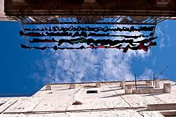Panni stesi all'esterno di un balcone di una casa nel borgo antico di Ostuni, in contrasto con il cielo azzurro