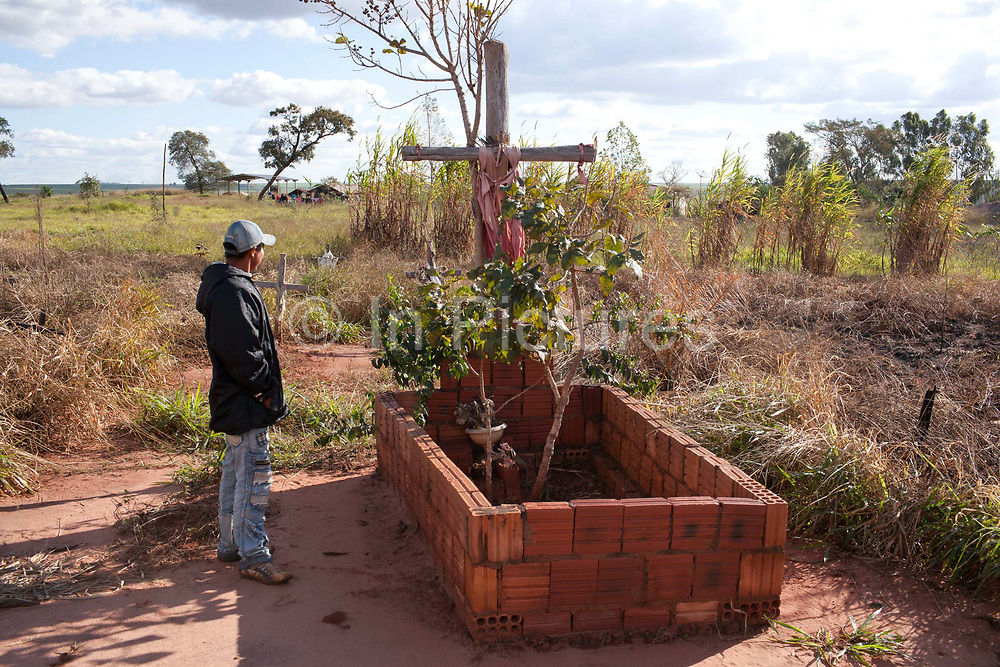 Young Guarani man looking at the grave of village tribe leader  Marcus Veron, who was alleged murdered by neighbouring farmers over land conflicts. The Guarani are one of the most populous indigenous populations in Brazil, but with the least amount of land. They mostly live in the State of Mato Grosso do Sul and Mato Grosso. Their tradtional way of life and ancestral land is increasingly at risk from large scale agribusiness and agriculture. There have been recorded cases and allegations of violence between owners of large farms and the Guarani communities in this region.