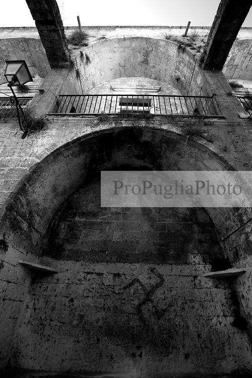 Ecco come si presenta la parte laterale sinistra del castello di Lizzano in provincia di Taranto. Le due arcate che si vedono in alto vennero costruite nel 1743 in seguito ad un terremoto. Lo stato di abbandono in cui si trova il castello non ha fatto altro che dare libero sfogo alla sua deturpazione: scritte, bottiglie rotte, carte circondano l'intero castello.