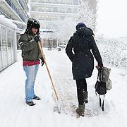 Nederland, Rotterdam, 17 december 2010. Weeralarm, zware sneeuwval in de Randstad. Medewerkers van bejaardentehuis Humanitas, gekleed in dikke winterkleding en mutsen, maken het trottoir naar de ingang van het ouderenhuis vrij van sneeuw. Wegscheppen van sneeuw, pad maken in de sneeuw. Een vrouw maakt gebruik van het net schoongemaakte pad. Foto: David Rozing