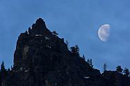 Waning gibbous moon setting over rock spire, Yosemite National Park, California