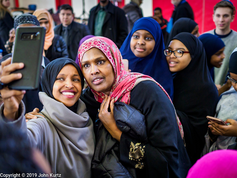 """16 MARCH 2019 - BLOOMINGTON, MINNESOTA, USA: Congresswoman ILHAM OMAR (D-MN) poses for """"selfies"""" with people from her district at Dar al Farooq Center in Bloomington. She is the first Somali-American elected to congress. An interdenominational crowd of about 1,000 people came to the center to protest white supremacy and religious intolerance and to support Muslims in New Zealand who were massacred by a white supremacist Friday. The Twin Cities has a large Muslim community following decades of Somali immigration to Minnesota. There are about 45,000 people of Somali descent in the Twin Cities.    PHOTO BY JACK KURTZ"""